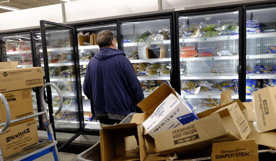 A worker restocks the frozen section at the Meijer store, Monday, March 16, 2020, in Whitestown, Ind. People concerned with the coronavirus have been shopping ahead and emptying store shelves. (AP Photo/Darron Cummings)