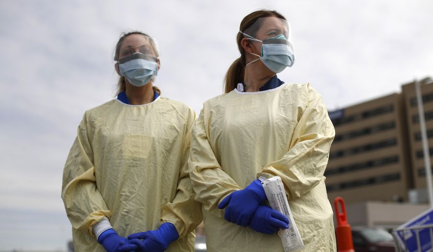 Physicians Assistant Jessica Hamilton, left, and Amena Beslic RN holds a swab and test tube kit to test people for COVID-19 at a drive through station set up in the parking lot of the Beaumont Hospital in Royal Oak, Mich., Monday, March 16, 2020. (AP Photo/Paul Sancya)