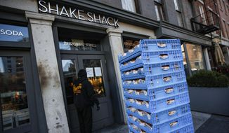 A bread delivery is made to a Shake Shack restaurant in the Brooklyn borough of New York, Monday, March 16, 2020.  Mayor Bill De Blasio is set to sign an executive order Monday shutting bars and restaurants. The order, which takes effect Tuesday, limits food service to takeout and delivery only.  (AP Photo/John Minchillo)