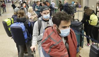 Masked travelers stand in line with luggage before getting to the ticket counter at the Salt Lake City International Airport Sunday, March 15, 2020, in Salt Lake City. For most people, the new coronavirus causes only mild or moderate symptoms, such as fever and cough. For some, especially older adults and people with existing health problems, it can cause more severe illness, including pneumonia.(AP Photo/Rick Bowmer)