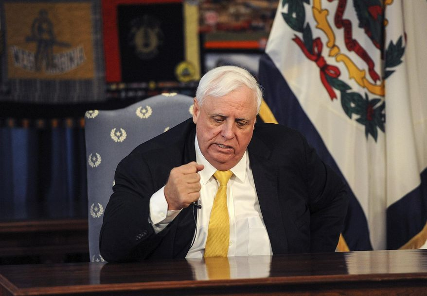 West Virginia Gov. Jim Justice pounds the table at the conclusion of his press conference saying the state can beat the coronavirus challenge, Friday, March 13, 2020 at the state Capitol in Charleston, W.Va. Justice announced that all schools are to be closed by the end of the school day Friday. (Chris Dorst/Charleston Gazette-Mail via AP)