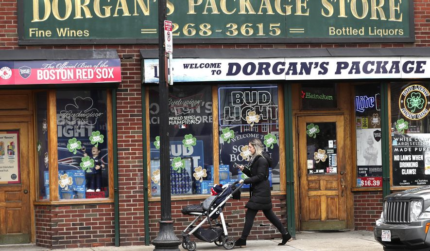 A woman pushes a stroller past a liquor store on a nearly empty sidewalk on Broadway on St. Patrick's Day in the South Boston neighborhood of Boston, Tuesday, March 17, 2020. For most people, the new coronavirus causes only mild or moderate symptoms. For some, it can cause more severe illness, especially in older adults and people with existing health problems. (AP Photo/Charles Krupa)