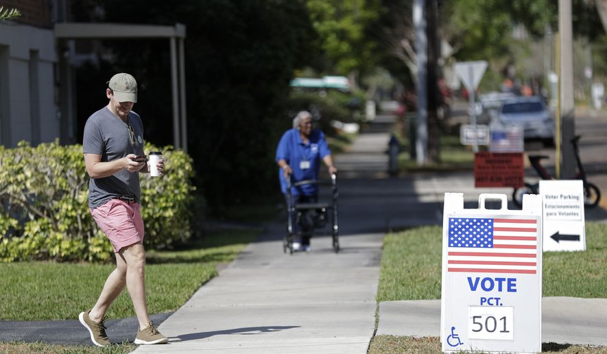 A voter, left, leaves a polling station after voting in Florida's primary election, Tuesday, March 17, 2020, in Orlando, Fla. As Florida officials try to contain the spread of the coronavirus, the state's voters headed to the polls and cast ballots in the Democratic presidential primary. (AP Photo/John Raoux) ** FILE **