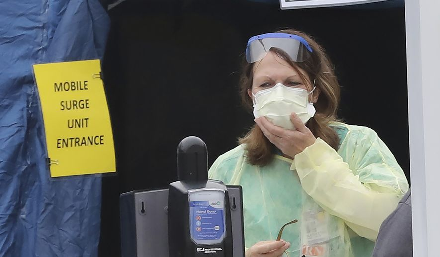 A nurse stands outside the entrance to the mobile surge unit tent for coronavirus testing outside the emergency entrance at WellStar Kennestone Hospital for patients who are being tested for COVID-19 on Tuesday, March 17, 2020, in Mariett, Ga. (Curtis Compton/Atlanta Journal-Constitution via AP(