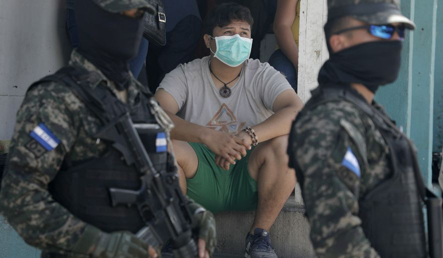 A resident wearing a protective mask watches from a stoop as soldiers and police cordon off the Lincoln neighborhood to prevent residents from leaving, after multiple people tested positive for the new coronavirus, in Tegucigalpa, Honduras, Tuesday, March 17, 2020. For most people, the new coronavirus causes only mild or moderate symptoms. For some, it can cause more severe illness, especially in older adults and people with existing health problems. (AP Photo/Elmer Martinez)