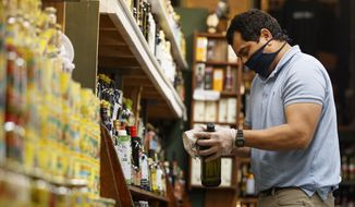 Tony Sanchez, wearing disposable gloves and a homemade mask made from a cut up t-shirt to help fight the coronavirus outbreak, cleans and sanitizes a bottle of olive oil at A. Litteri Italian Specialty Delicatessen at Union Market in Washington, Tuesday, March, 17, 2020. (AP Photo/Carolyn Kaster)