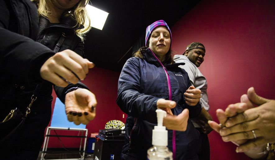 Sharon Trask and other voters use hand sanitizer as they stand in line to vote at Lincoln Lodge Polling station, 1st ward, Tuesday, March 17  2020 in Chicago.  Voters across the state are getting the chance to decide competitive primary races for the U.S. House and the Illinois Supreme Court, with concerns about the coronavirus looming large. Election officials have been promoting voting early and casting ballots by mail in an attempt to control crowds and curb the spread. The vast majority of people recover from the new coronavirus. According to the World  Health Organization, most people recover in about two to six weeks, depending on the severity of the illness. (James Foster/Chicago Sun-Times via AP)
