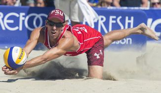 FILE - In this Aug. 23, 2015, filer photo, United States' Nick Lucena digs out a ball during the final match at the FIVB World Series of Beach Volleyball event in Long Beach, Calif. Organizers of the AVP beach volleyball tour gathered at their Orange County war room to try to salvage as much as possible of their season as the cancellations mounted in the sports world. Ideas tossed out included everything from a fan-free setup on a local beach to playing in front of a green screen in a TV studio. But with the suspension of the NBA season, it became obvious that scrapping any events before June was the only choice.(Michael Goulding/The Orange County Register via AP, File)