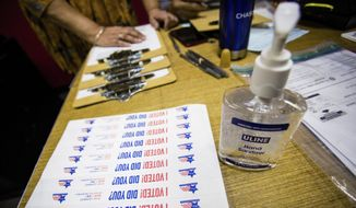 Hand sanitizer and stickers are set up at the Lincoln Lodge Polling Station, 1st ward, Tuesday, March 17th, 2020 in Chicago. (James Foster/Chicago Sun-Times via AP) ** FILE **