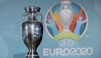 FILE - In this Thursday, Oct. 27, 2016 file photo the Euro soccer championships trophy is seen in front of the logo during the presentation of Munich's logo as one of the host cities of the Euro 2020 European soccer championships in Munich, Germany. UEFA, are set to make a final decision when the UEFA executive committee meets on Tuesday March 17, 2020 after talks with clubs and leagues, about possibly delaying the Euro 2020 soccer tournament by a year as the continent grapples with the outbreak of the coronavirus. (AP Photo/Matthias Schrader, File)