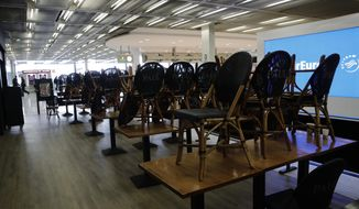Chairs pile up at cafe at Orly airport Tuesday, March 17, 2020, south of Paris. French President Emmanuel Macron announced strong restrictions on freedom of movement in a bid to counter the new coronavirus, as the European Union closed its external borders to foreign travelers. For most people, the new coronavirus causes only mild or moderate symptoms. For some it can cause more severe illness. (AP Photo/Christophe Ena)