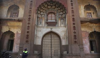 A private security guard walks past the gate of Safdarjung's Tomb, a sandstone and marble mausoleum built in 1754, closed as a precaution against the spreading of new coronavirus in New Delhi, India, Tuesday, March 17, 2020. For most people, the new coronavirus causes only mild or moderate symptoms. For some, it can cause more severe illness, especially in older adults and people with existing health problems. (AP Photo/Manish Swarup)
