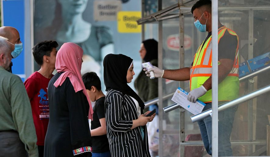 Customers of a convenience store have their temperature checked and are given gloves before they are allowed to enter as a precaution against the COVID-19 coronavirus, in Baghdad, Iraq, Monday, March 16, 2020.   Iraq announced a weeklong curfew to help fight the spread of coronavirus, late Sunday.   For most people, the new coronavirus causes only mild or moderate symptoms. For some it can cause more severe illness.  (AP Photo/Hadi Mizban)