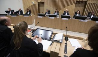 Lawyers Boudewijn van Eijck, left, and Sabine ten Doesschate, second left, lawyers for one of the four accused, judges, rear right, and the public prosecution, rear left, are seen at the start of the trial of four men charged with murder over the downing of Malaysia Airlines flight 17, at Schiphol airport, near Amsterdam, Netherlands, Monday, March 9, 2020. A missile fired from territory controlled by pro-Russian rebels in Ukraine in 2014, tore the MH17 passenger jet apart killing all 298 people on board. (AP Photo/Peter Dejong)