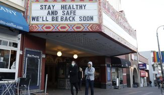 A man wears a mask while walking under the marquee of The Castro Theatre in San Francisco, Monday, March 16, 2020. Officials in six San Francisco Bay Area counties issued a shelter-in-place mandate Monday affecting nearly 7 million people, including the city of San Francisco itself. The order says residents must stay inside and venture out only for necessities for three weeks starting Tuesday in a desperate attempt by officials to curb the spread of the novel coronavirus. (AP Photo/Jeff Chiu)