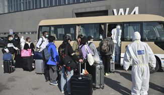 In this March 17, 2020, photo released by China's Xinhua News Agency, workers in protective suits watch as travelers board a shuttle bus at the New China International Exhibition Center, which has been converted into a facility to screen international flight passengers arriving in Beijing. As the pandemic expanded its reach, China and South Korea were trying to hold their hard-fought gains. China is quarantining new arrivals, who in recent days have accounted for an increasing number of cases, and South Korea starting Thursday will increase screenings of all overseas arrivals. The virus causes only mild or moderate symptoms, such as fever and cough, for most people, but severe illness is more likely in the elderly and people with existing health problems. (Peng Ziyang/Xinhua via AP)