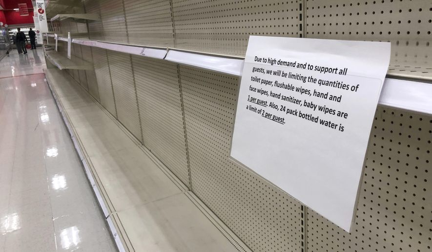 A sign hangs on the empty shelves to tell shoppers the limit on purchases of certain products, in a Target store Tuesday, March 17, 2020, in the Denver suburb of Lakewood, Colo. (AP Photo/David Zalubowski)