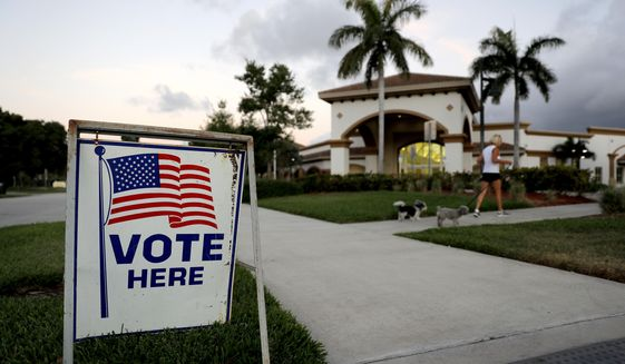 In this file photo, a sign is placed outside of a polling place at the Boca Raton Library during the Florida primary election, Tuesday, March 17, 2020, in Boca Raton, Fla.   (AP Photo/Julio Cortez)  **FILE**