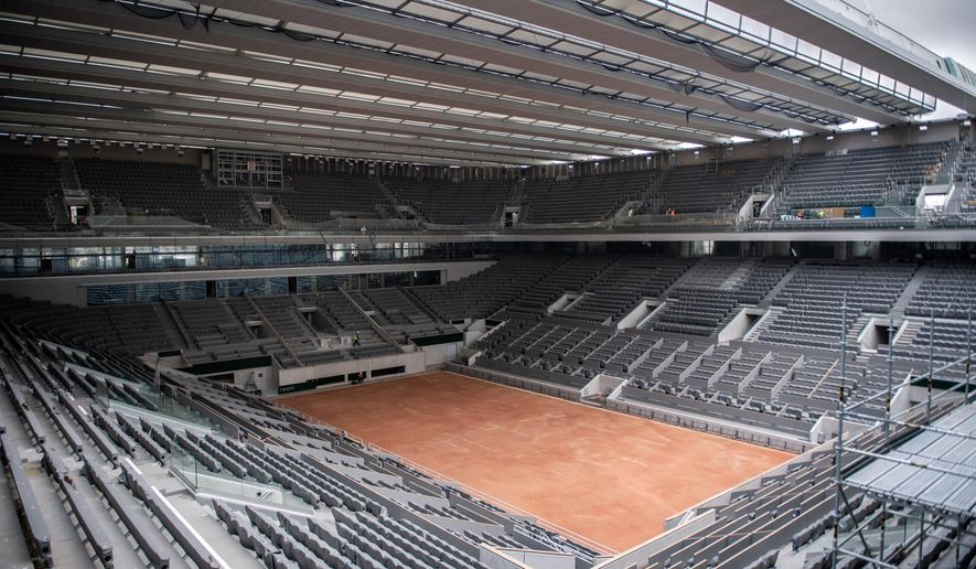 FILE - In this Feb. 5, 2020, file photo, construction work of the newly built roof of the Philippe Chatrier center court is pictured at Roland Garros stadium in Paris. The French Open has been postponed because of the coronavirus. The French Tennis Federation announced Tuesday, March 17, 2020, that the clay-court event will run from Sept. 20 to Oct. 4. Main draw competition was supposed to start on May 24. (Martin Bureau/Pool via AP, File)