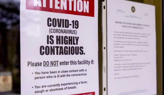 Signs are posted about the coronavirus on the doors of the Oklahoma State Department of Education in Oklahoma City, Monday, March 16, 2020. Oklahoma's State Superintendent of Public Instruction Joy Hofmeister announced the closing of public school till April 6 to combat the spread of the coronavirus. (Chris Landsberger/The Oklahoman via AP)