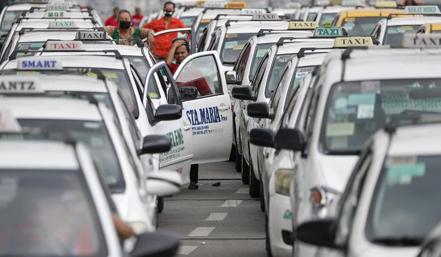 A taxi driver reacts as they wait to show their ID and car documents to police who instructed them to stop operations while the government implements localized quarantining as a precautionary measure against the spread of the new coronavirus in Manila, Philippines, early Tuesday, March 17, 2020. For most people, the new coronavirus causes only mild or moderate symptoms. For some, it can cause more severe illness, especially in older adults and people with existing health problems. (AP Photo/Aaron Favila)