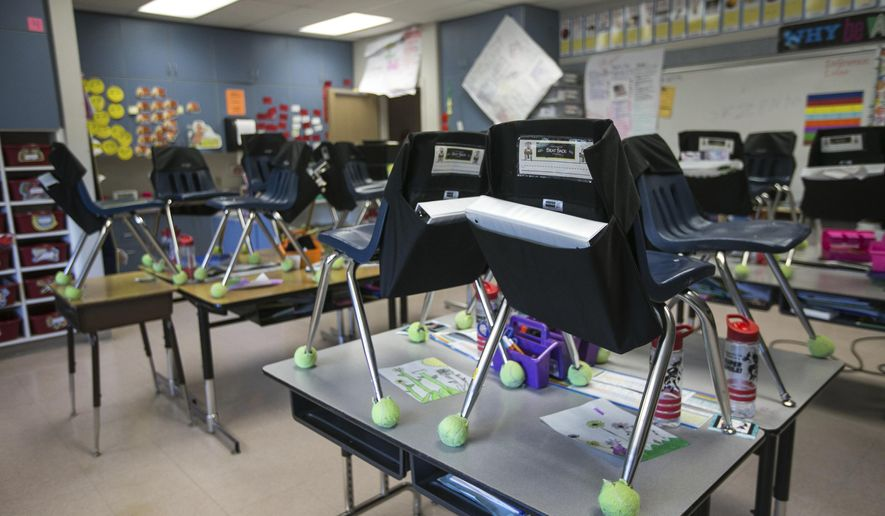 Student's chairs are stacked on top of desks in an empty classroom at closed Robertson Elementary School, March 16, 2020, in Yakima, Wash. (Amanda Ray/Yakima Herald-Republic via AP)