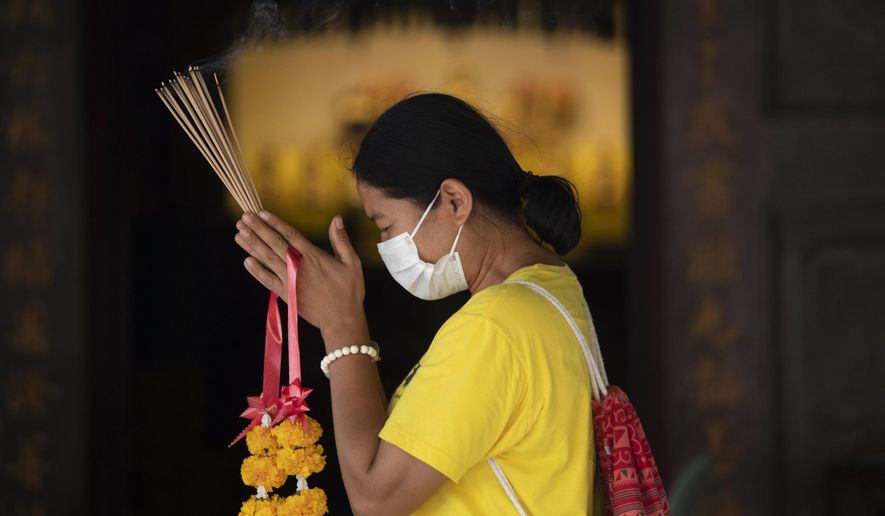 A woman wears a protective mask as she offers incenses during prayers at the Leng Nuei Yee Chinese temple in Bangkok, Thailand, Monday, March 16, 2020. For most people, the new coronavirus causes only mild or moderate symptoms. For some it can cause more severe illness. (AP Photo/Sakchai Lalit)