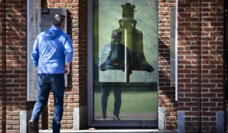 A visitor views the Liberty Bell from outside as the center is temporarily closed for cleaning in Philadelphia, Monday, March 16, 2020.  In a new front to slow the spread of the new coronavirus in Pennsylvania, Gov. Tom Wolf ordered all restaurants and bars to close their dine-in facilities in five heavily populated counties starting Monday. According to the World  Health Organization, most people recover in about two to six weeks, depending on the severity of the illness.  (AP Photo/Matt Rourke)