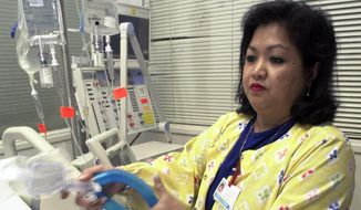 In this May 25, 2005, file photo, Lovely R. Suanino, a respiratory therapist at Newark Beth Israel Medical Center in Newark, N.J., demonstrates setting up a ventilator in the intensive care unit of the hospital. U.S. hospitals bracing for a possible onslaught of coronavirus patients with pneumonia and other breathing difficulties could face a critical shortage of mechanical ventilators and health care workers to operate them. (AP Photo/Mike Derer, File)