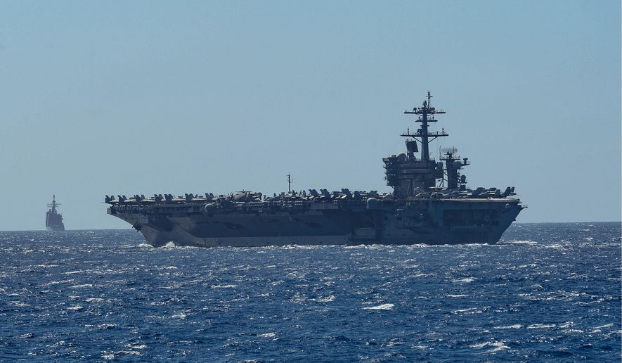 The aircraft carrier USS Theodore Roosevelt and the Ticonderoga-class guided-missile cruiser USS Bunker Hill are among warships at risk of electromagnetic attacks while transiting the South China Sea. (U.S. Navy) ** FILE **