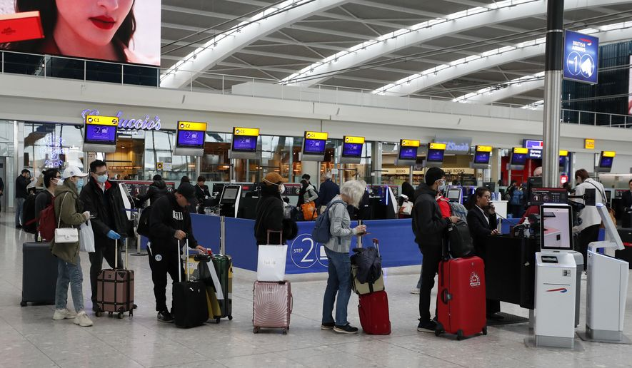 People queue at ticket machines at Heathrow airport in London, Wednesday, March 18, 2020. For most people, the new coronavirus causes only mild or moderate symptoms, such as fever and cough. For some, especially older adults and people with existing health problems, it can cause more severe illness, including pneumonia. (AP Photo/Frank Augstein)