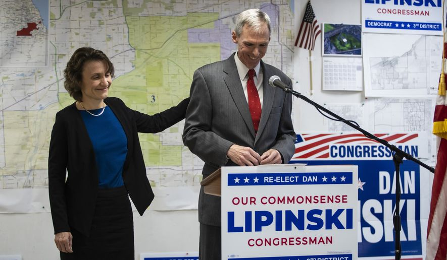 Judy Lipinski touches the back of her husband U.S. Rep. Dan Lipinski as he concedes the Democratic primary election to Progressive Marie Newman during a press conference at his election headquarters in Oak Lawn, Ill., Wednesday afternoon, March 18, 2020. (Ashlee Rezin Garcia/Chicago Sun-Times via AP)