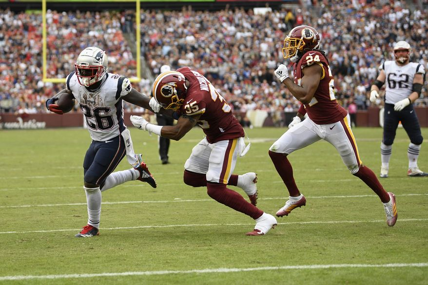 New England Patriots running back Sony Michel (26) runs with the ball against Washington Redskins free safety Montae Nicholson (35) and cornerback Josh Norman (24) during the second half of an NFL football game, Sunday, Oct. 6, 2019, in Washington. (AP Photo/Nick Wass)  **FILE**