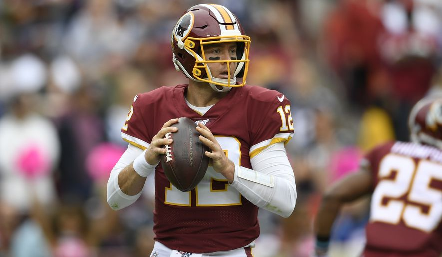 Washington Redskins quarterback Colt McCoy (12) looks to pass during the first half of an NFL football game against the New England Patriots, Sunday, Oct. 6, 2019, in Washington. (AP Photo/Nick Wass)