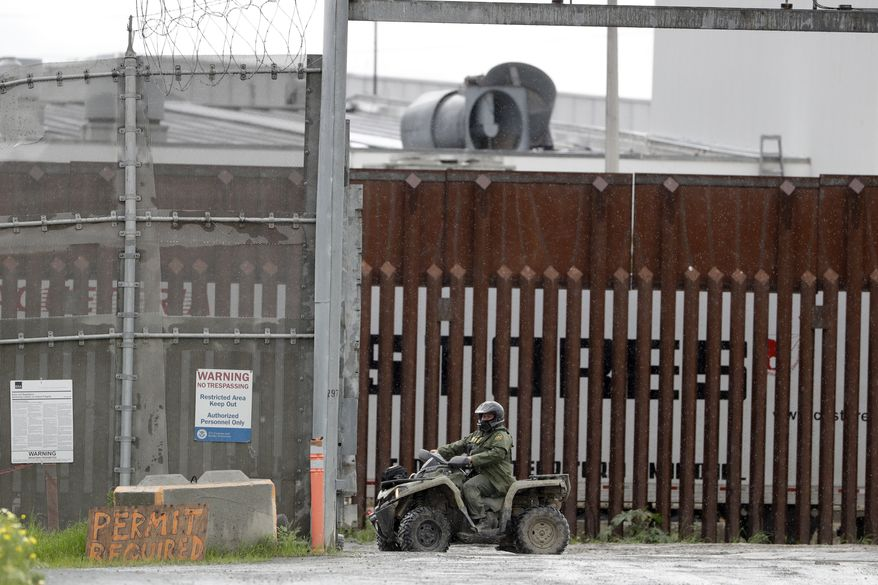 A border patrol agent rides a vehicle along a border wall separating Tijuana, Mexico, from San Diego, Wednesday, March 18, 2020, in San Diego. (AP Photo/Gregory Bull)