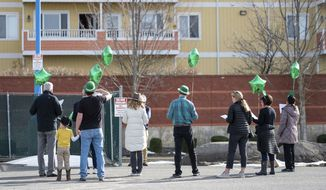 Friends and family of Margaret Presley, age 97, serenade her with Irish songs while she listens from a balcony at the South Hill Village, Tuesday, March 17, 2020, in Spokane, Wash. Presley is currently semi-quarantined in the assisted living community because of the coronavirus. (Colin Mulvany/The Spokesman-Review via AP)