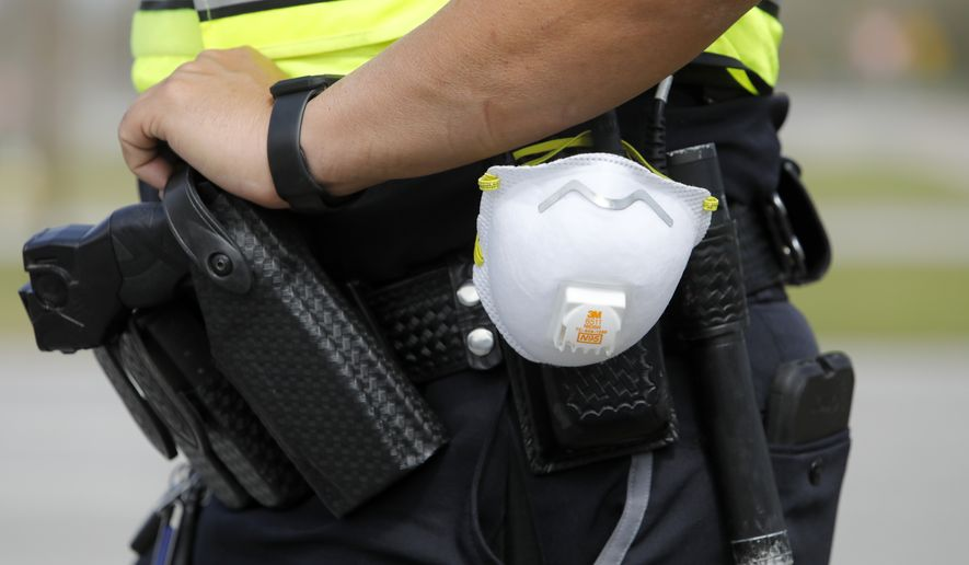 In this March 16, 2020, photo a North Charleston police officer carries a protective mask around his gun belt while working traffic at Roper St. Francis' North Charleston office in North Charleston, S.C. The coronavirus has the potential to profoundly change law enforcement in the U.S.  as police departments are shifting resources and changing how they police while the virus strikes. (AP Photo/Mic Smith, File)