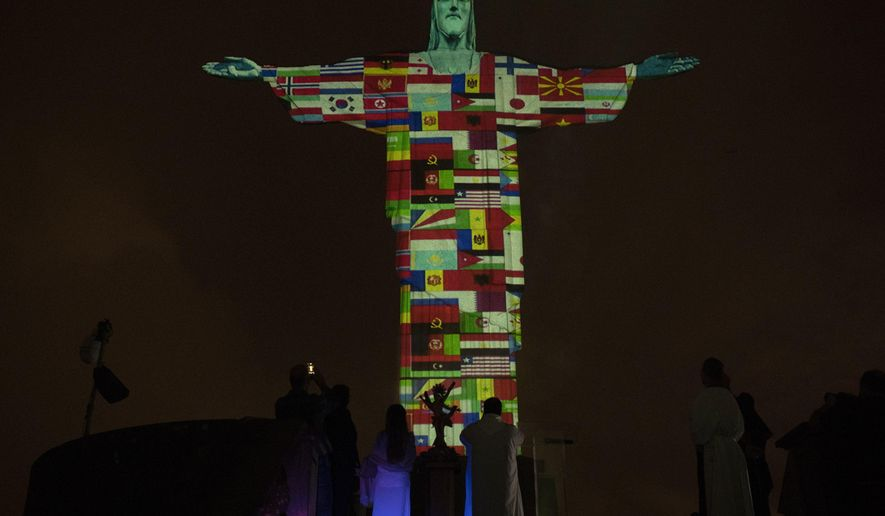 Rio's Christ the Redeemer statue is lit up with the flags of countries currently afflicted by the new coronavirus in Rio de Janeiro, Brazil, Wednesday, March 18, 2020. For most people COVID-19 causes mild or moderate symptoms. For others, especially the elderly and people with existing health problems, it can cause many other serious illnesses, including pneumonia. (AP Photo/Silvia Izquierdo)