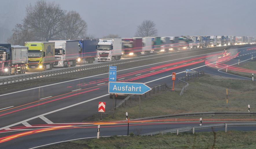 Trucks are jammed in the early morning on Autobahn 12 in front of the German-Polish border crossing near Frankfurt (Oder), Germany, Wednesday, March 18, 2020. In order to make it more difficult for the corona virus to spread, Poland had reintroduced controls at the border crossings to Germany. For most people, the new coronavirus causes only mild or moderate symptoms, such as fever and cough. For some, especially older adults and people with existing health problems, it can cause more severe illness, including pneumonia. (Patrick Pleul/dpa via AP)