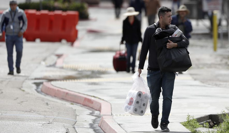 A man carries toilet paper after crossing the border from Tijuana, Mexico, to San Diego, Wednesday, March 18, 2020, in San Diego. (AP Photo/Gregory Bull)