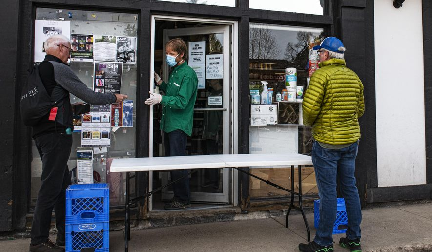 A Carl's Pharmacy employee, wearing a mask and gloves against the coronavirus, reaches out the door to accept payment from a customer Tuesday, March 17, 2020, in Aspen, Colo. (Kelsey Brunner/The Aspen Times)/The Aspen Times via AP)