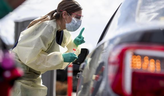 In this file photo, Ashley Layton, an LPN at St. Luke's Meridian Medical Center, communicates with a person before taking swab sample at a special outdoor drive-thru screening station for COVID-19   coronavirus Tuesday, March 17, 2020.  (Darin Oswald/Idaho Statesman via AP)  **FILE**