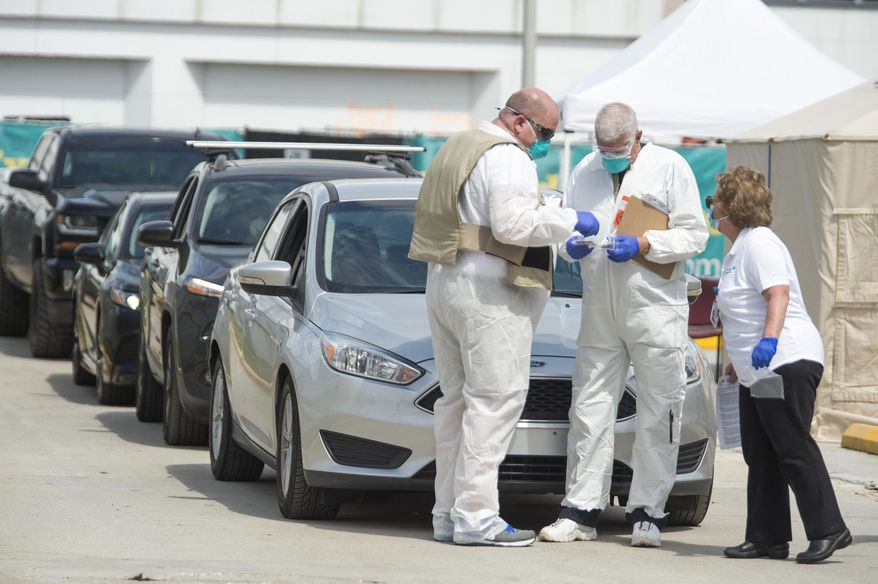 Health workers screen for the COVID-19 coronavirus at a drive-through outside of West Jefferson Medical Center in Marrero, La., on Tuesday, March 17, 2020. (Chris Granger/The Advocate via AP)