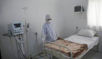 FILE - In this, Sunday, March 15, 2020 file photo, a medical staff member works on setting up an isolation room at a coronavirus quarantine ward at a hospital in Sanaa, Yemen. In conflict zones across the Middle East, the specter of the coronavirus looms large. Authorities in Yemen, Libya, Syria, Afghanistan and the Gaza Strip warn that health care systems gutted by years of war and unrest have left millions of people doubly vulnerable to the pandemic. For most people, the virus causes only mild or moderate symptoms. For some it can cause more severe illness. (AP Photo/Hani Mohammed, File)