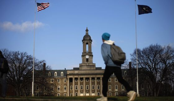 In this Friday, Nov. 11, 2011, file photo, a student walks in front of the Old Main building on the Penn State campus in State College, Pa. The university on Wednesday, March 18, 2020, canceled in-person classes for the rest of the spring semester, citing the coronavirus pandemic, as state officials announced a 40% jump in the number of confirmed cases. (AP Photo/Matt Rourke, File)