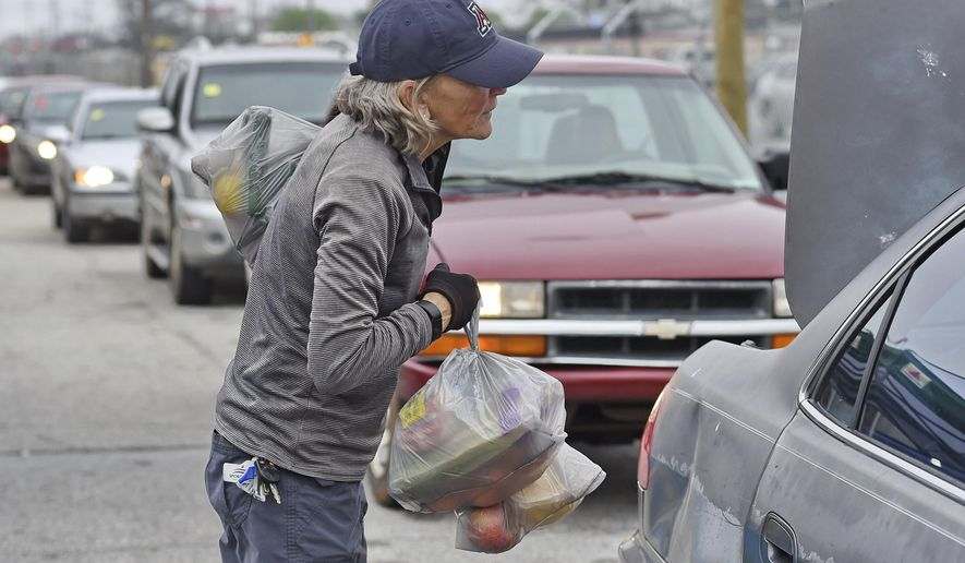 A volunteer loads groceries at a drive through and pick up location at Harvest Hope Food Bank Wednesday, March 18, 2020, in Greenville, S.C. Harvest Hope helps low income families and senior citizens. (AP Photo/Richard Shiro)