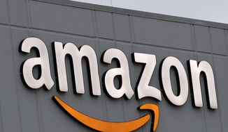 A sign is lit on the facade of an Amazon fulfillment center, Thursday, March 19, 2020, on Staten Island in New York. The company plans to hire another 100,000 new workers in their fulfillment centers to fill increased customer demand during the coronavirus outbreak in which many workers are working from home an discouraged from going out. (AP Photo/Kathy Willens)