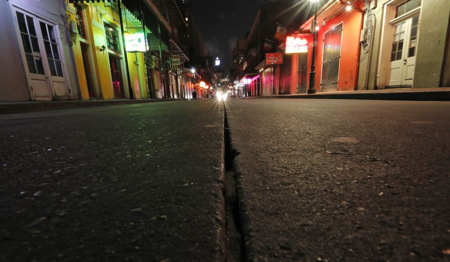 A view of the nearly deserted scene on Bourbon Street, which is normally bustling with tourists and revelers, in the French Quarter of New Orleans, Thursday, March 19, 2020. Louisiana Governor John Bel Edwards and New Orleans Mayor Latoya Cantrell have ordered all restaurants and bars to close except for takeout, and asked residents to remain home and maintain social distancing from others when outside, due to the COVID-19 virus pandemic. (AP Photo/Gerald Herbert)