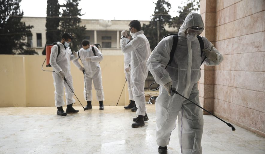 Members of a humanitarian aid agency disinfect Ibn Sina hospital as prevention against coronavirus in the city of Idlib, Syria, Thursday, March 19, 2020. (AP Photo/Ghaith Alsayed)