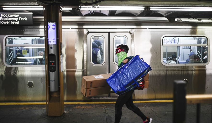 A subway customer wears a ski-mask and bandana face covering while exiting a station as COVID-19 concerns drive down ridership, Thursday, March 19, 2020, in New York. Gov. Andrew Cuomo tightened work-from-home rules Thursday as confirmed cases continued to climb in New York, an expected jump as testing becomes more widespread. But he stressed that roadblocks and martial law for New York City were merely rumors. (AP Photo/John Minchillo)